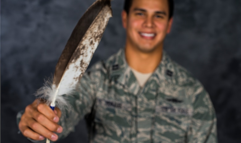 Capt. Myles Morales poses for a photo holding his eagle feather Dec. 3, 2014, at Moody Air Force Base, Ga. Morales received the eagle feather during a naming ceremony held in his honor by the Lakota Sioux tribe on Standing Rock Reservation, South Dakota. Morales is the 336th Recruiting Squadron support flight commander. (U.S. Air Force photo/Airman 1st Class Ceaira Tinsley)