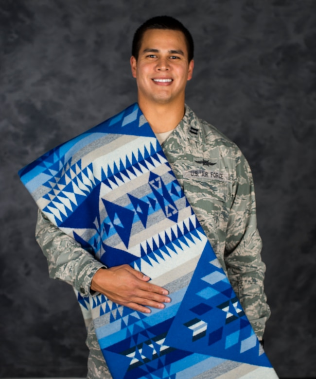 Capt. Myles Morales poses for a photo with his Pendleton quilt Dec. 3, 2014, at Moody Air Force Base, Ga. Morales' native name is Wanbli Kinyan Gli and it translates to 'the eagle flies home.' Morales is the 336th Recruiting Squadron support flight commander. (U.S. Air Force photo/Airman 1st Class Ceaira Tinsley)