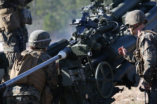 Cpl. Allison M. Devries, left, field artillery cannoneer, Battery A, Ground Combat Element Integrated Task Force, loads an M777 A2 howitzer during a live-fire exercise at Range GP 7 aboard Marine Corps Base Camp Lejeune, North Carolina, Dec. 17, 2014. From October 2014 to July 2015, the Ground Combat Element Integrated Task Force will conduct individual and collective skills training in designated combat arms occupational specialties in order to facilitate the standards based assessment of the physical performance of Marines in a simulated operating environment performing specific ground combat arms tasks. (U.S. Marine Corps photo by Cpl. Paul S. Martinez/Released)