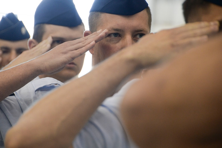Airmen assigned to 12th Air Force (Air Forces Southern) salute during the playing of the national anthem during the 12th Air Force (Air Forces Southern) change of command ceremony at Davis-Monthan AFB, Ariz., Dec. 19, 2014. Lt. Gen. Tod Wolters relinquished command to Lt. Gen. Chris Nowland. (U.S. Air Force photo by Staff Sgt. Adam Grant/Released)