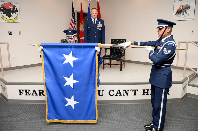 Lt. Gen. Chris Nowland, 12th Air Force (Air Forces Southern) incoming commander, observes as members of the Davis-Monthan AFB honor guard present him with his flag on Dec. 19, 2014. Nowland comes to Tucson from his previous assignment as the Chief of Staff, Headquarters United States Southern Command, where he was responsible for successfully integrating and synchronizing the efforts of nine directorates and 16 special staff offices in support of the Combatant Commander's Theater Campaign Plan. (U.S. Air Force photo by Staff Sgt. Adam Grant/Released)
