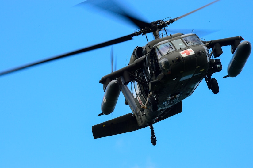 A UH-60 Black Hawk helicopter from the 1-228th Aviation Battalion circles around an area of Lake Yojoa looking for a rescue mannequin, Honduras, Dec. 18, 2014.   The 1-228th AVN BN spent the afternoon practicing overwater hoist training.  The overwater hoist training was held to ensure members of Joint Task Force-Bravo are planning and preparing for crisis and contingency response as part of U.S. Southern Command's mission. Contingency planning prepares the command for various scenarios that pose the greatest probability of challenging our regional partners or threatening our national interests.  (U.S. Air Force photo/Tech. Sgt. Heather Redman)