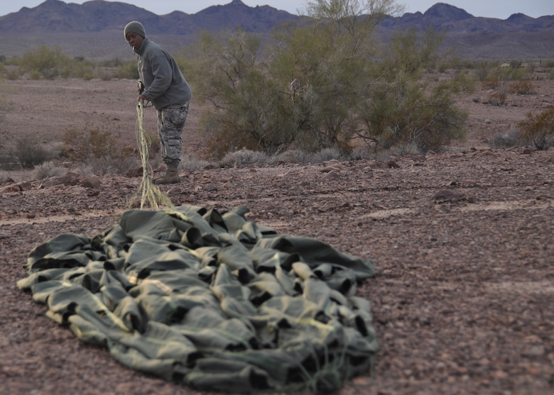 Staff Sgt. Latresha Peterson, member of the 80th Aerial Port Squadron, untangles a parachute from a pallet at Yuma, Arizona, Dec. 15, 2014. The pallet was dropped from a C-130 at an altitude of 18,000 feet. (U.S. Air Force photo by SrA Miles Wilson)