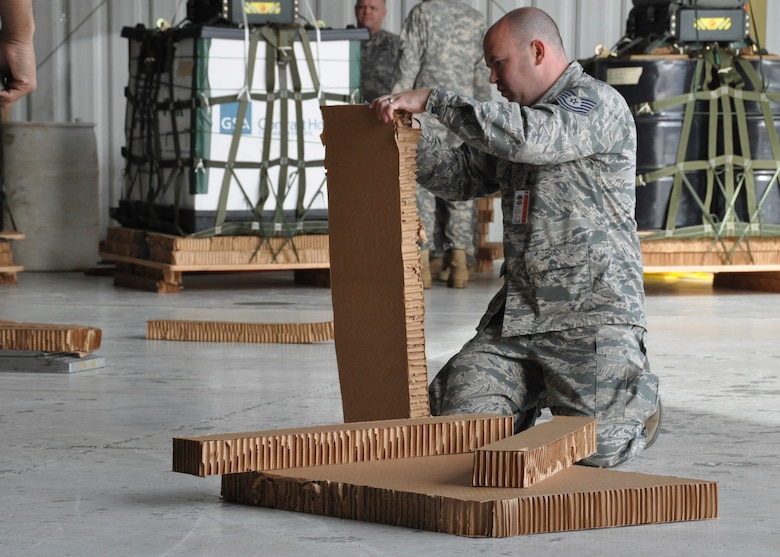 Tech. Sgt. Jeremy Wetherington, member of the 80th Aerial Port Squadron, cuts strips of honeycomb cardboard to place under pallets at Yuma, Arizona, Dec. 15, 2014. The pallets were to be airdropped from C-130's during Desert University Training. (U.S. Air Force Photo by Senior Airman Miles Wilson)