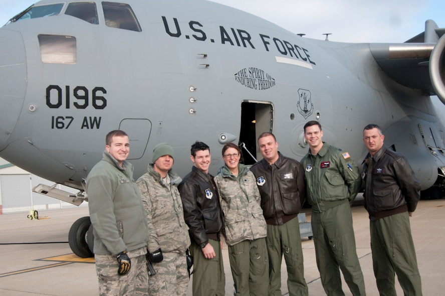 After the first local training sortie of a C-17 at the 167th Airlift Wing, West Virginia Air National Guard base in Martinsburg, W.Va., Dec. 18, ground crew and those aboard the historic flight stand in front of the aircraft. From left to right: Staff Sgt. Mark A. Kelley Jr., Master Sgt. Joseph S. Bosacco, Capt. Justin S. McCabe, Lt. Col. Lisa Windle, Master Sgt. Charles R.D. Moore Capt. Christopher K. Nary and Chief Master Sgt. Leslie Y. Morris.  (Air National Guard photo by Staff Sgt. Sherree Grebenstein/released)