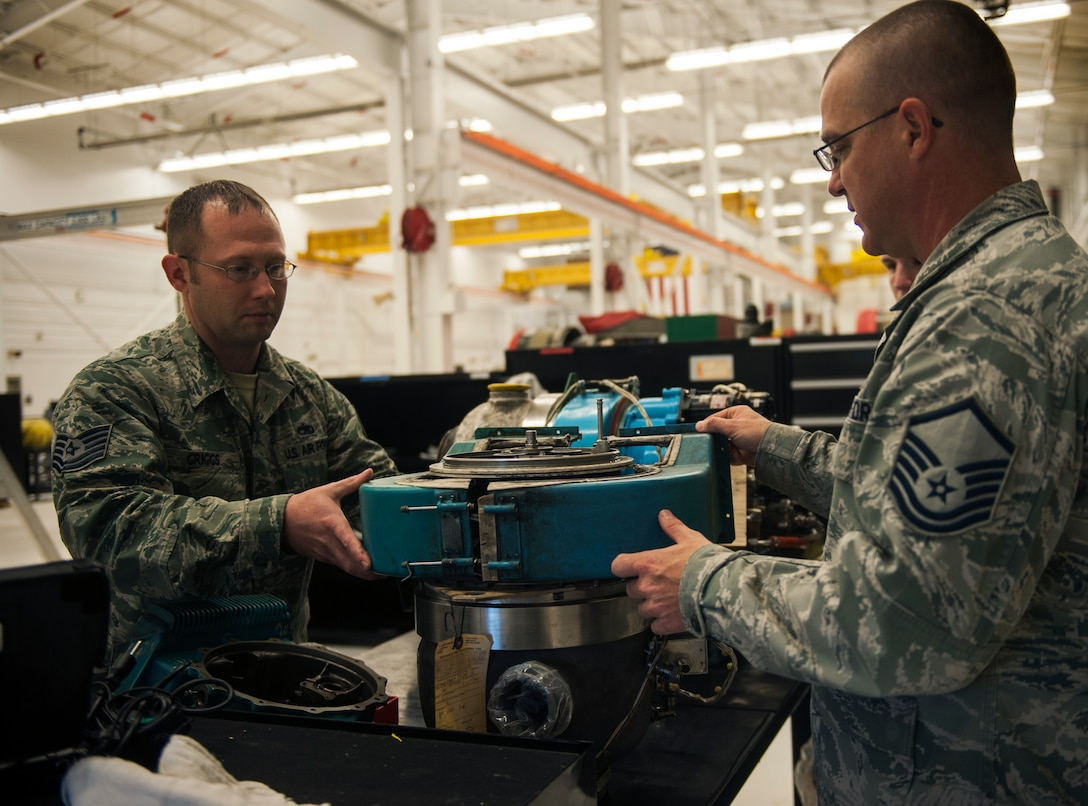 U.S. Air Force Master Sgt. Eric Horton, right, and Tech. Sgt. Michael Griggs, 23d Component Maintenance Squadron aerospace propulsion craftsmen, attach a gear box to a GTCP-3650 auxiliary power unit (APU) Dec. 15, 2014, at Moody Air Force Base, Ga. The APU is a small gas turbine engine that provides power to the TF-34 engine on the A-10C Thunderbolt II. (U.S. Air Force photo by Senior Airman Olivia Bumpers/Released)