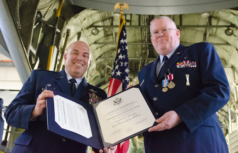 Col. Ken Dale (left), commander of the 123rd Airlift Wing, presents Chaplain (Lt. Col.) Patrick Cooney, the Kentucky Air National Guard's Catholic and wing chaplain, with Cooney's retirement certificate during a ceremony at the Kentucky Air National Guard Base in Louisville, Ky., on Dec. 7, 2014. Cooney is retiring after more than 30 years of service to the active-duty Air Force and Air National Guard. (U.S. Air National Guard photo by Senior Airman Joshua Horton)