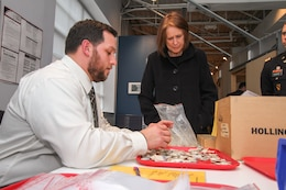 ALEXANDRIA, Va. -- Nick Gervasoni , a Veterans Curation Program laboratory technician, shows Jo-Ellen Darcy, the  assistant secretary of the Army for civil works, on Dec. 3, 2014, how he sorts and documents ceramics recovered from Fort Norfolk in the late 1970. Giacobozzi is a military veteran enrolled in the curation program, which provides recently separated military veterans with employment and archaeological training while also providing the veterans with resume writing assistance and interview skills over a five month period.  (U.S. Army photo/Patrick Bloodgood)