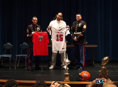 Benning Potoae (center), a defensive end for the Lakes High School Lancers varsity football team and 18-year-old native of Dupont, Washington, receives his 2015 Semper Fidelis All-American Bowl jersey from Sgt. Daniel Pluth (left), a Tacoma recruiter, and Staff Sgt. Cody Branham (right), the recruiter in charge of Recruiting Substation Puyallup, during a ceremony at Lakes High School in Lakewood, Washington, Dec. 16, 2014. Potoae is among approximately 100 student athletes from across the nation selected to participate in the game at the StubHub Center in Carson, Calif., Jan. 4, 2015. He joins cornerback Austin Joyner from Marysville-Pilchuck High School and offensive tackle Shane Lemieux from Yakima's West Valley High School as the Washington State players selected for the 2015 game. (U.S. Marine Corps photo by Sgt. Reece Lodder)
