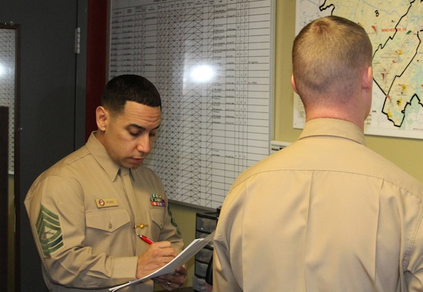 U.S. Marine Corps Master Sgt. Michael Rivas, a Lorain, Ohio native and the recruiter instructor for Recruiting Station Frederick talks with Sgt. Joshua Glenn, the staff noncommissioned officer in charge of Recruiting Sub-Station Winchester during a systematic recruiting inspection in Winchester, Virginia, Nov. 25, 2014. Rivas was awarded 4th Marine Corps District Recruiter Instructor of the Year for 2014.