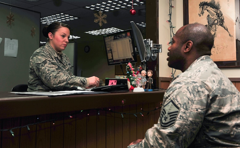 Senior Airman Elizabeth Heaton, 51st Comptroller Squadron customer service technician, out-processes Master Sgt. Marvin Wallace, 51st Fighter Wing Command Post NCO in charge, from finance Dec. 19, 2014 at Osan Air Base, Republic of Korea. Heaton is this week's Airman Spotlight winner. (U.S. Air Force photo by Senior Airman David Owsianka)