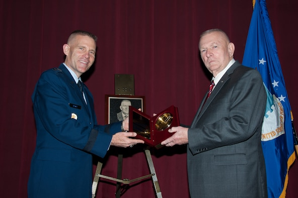 Lt. Gen. Steven Kwast, Air University commander, presents Gene Kranz with the Air Force ROTC Distinguished Alumni Award during a ceremony Dec. 16, 2014, at Maxwell Air Force Base, Alabama. Kranz, who received his commission through the ROTC program at Saint Louis University in 1954, was the flight director for the Apollo 13 mission in April 1970 that ended successfully following an explosion aboard the space capsule. Kranz was selected for the distinction because of his exceptional meritorious service to the Air Force and NASA for more than 40 years. (US Air Force photo by Melanie Rodgers Cox/Released)