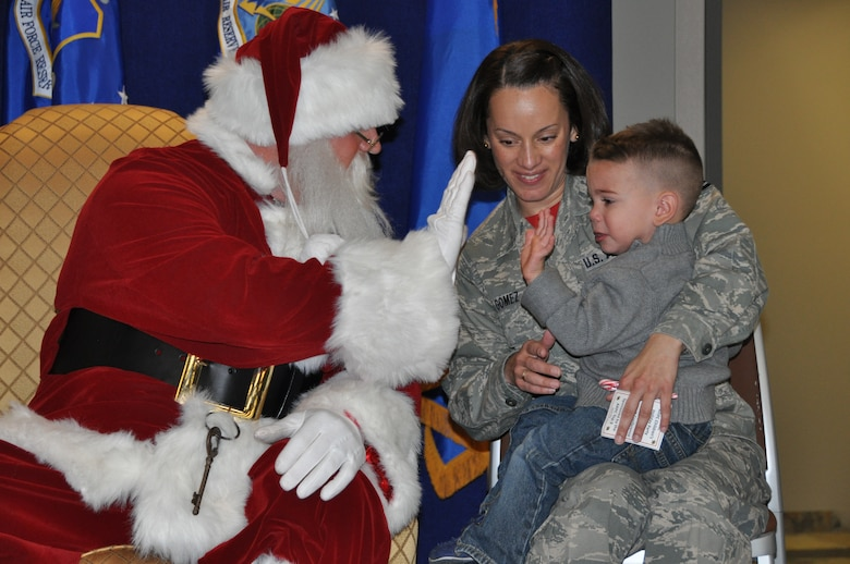 """Santa Claus high-fives a service member's child during his visit to the Air Reserve Personnel Center Dec. 19, 2014, on Buckley Air Force Base, Colo. Brig. Gen. Samuel """"Bo"""" Mahaney, ARPC commander, introduced Santa, Mrs. Claus and Sparkle the elf to excited families and children as he discussed the relationship with Santa Claus and the Air Force, which dates back decades. (U.S. Air Force photo/Tech. Sgt. Rob Hazelett)"""