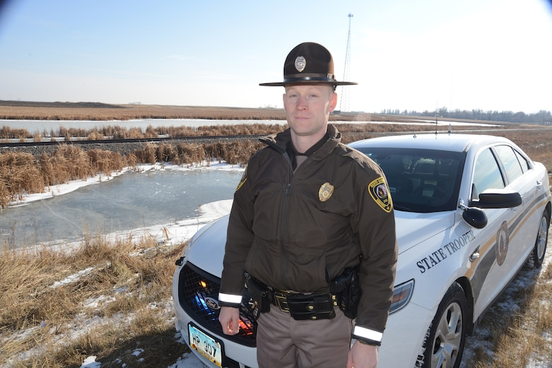 Master Sgt. Grant Lonski, of the 119th Security Forces Squadron, visits the accident scene that he responded to while performing his full-time North Dakota Highway Patrol duties near Churchs Ferry, North Dakota a week prior to the Nov. 18, 2014 return visit. Lonski was able to pull 81-year old accident victim Merti Kurtti from freezing cold water in the ditch behind him in the photo. (U.S. Air National Guard photo by Senior Master Sgt. David H. Lipp/Released)