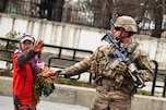 A U.S. soldier provides security as an Afghan child waves to International Security Assistance Force members as they pass by in Kabul, Afghanistan, Dec. 20, 2014.