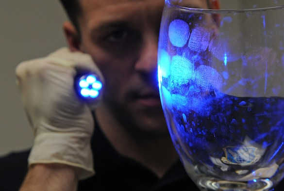 Special Agent Adam Deem shines light on a glass to reveal fingerprints on Barksdale Air Force Base, La. Deem dusted the glass with an orange powder that helps agents detect finger prints with ultraviolet light. Deem serves with Air Force Office of Special Investigation Detachment 219. (U.S. Air Force photo/Airman 1st Class Micaiah Anthony)