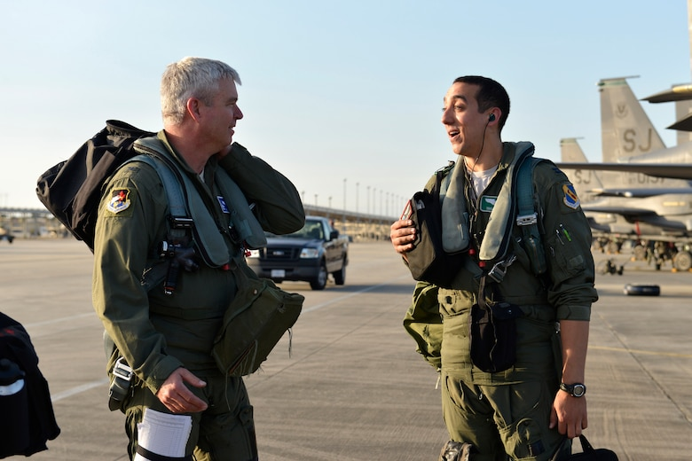 Col. Al Wimmer, left, exchanges a word with his son, Capt. Taylor Wight, before their dissimilar aircraft mission Dec. 12, 2014, at Tyndall Air Force Base, Fla. Wimmer is the director of Air Forces Northern's Operations and Information Operations Directorate and an F-16 Fighting Falcon pilot, and his son, Wight, is the assistant chief of training with the 335th Fighter Squadron at Seymour Johnson Air Force Base, N.C., and an F-15E Strike Eagle pilot. (U.S. Air Force photo/Master Sgt. Kurt Skoglund)