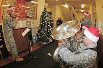 Members of the 1st Infantry Division Band's brass quintet perform Dec. 16 for employees at Garrison Headquarters on Main Post.  While Staff Sgt. Matthew Johnston, NCOIC, played the trombone, Sgt. Jose Hernandez, tuba, Spc. Chris Arnold, trumpet, and Sgt. Curtis Palmer, French horn, blended in playing several selections of holiday classics.