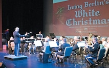 "Staff Sgt. Jason Ford (left), 1st Inf. Div. Band, conducts the joint 1st Inf. Div. and Junction City Community bands in a rendition of ""An Irving Berlin Christmas"" Dec. 14 at the C.L. Hoover Opera House, Junction City. The assembly of musicians performed the Sounds of the Season concert Dec. 12 to 14 featuring holiday favorites and new takes on classic carols."