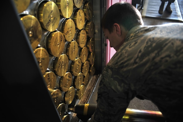A maintainer with the 27th Special Operations Maintenance Squadron places a 105 millimeter ammo round in a storage container Dec. 18, 2014 at Cannon Air Force Base, N.M. Munition specialists maintain and recondition munitions, munitions handling equipment and munitions maintenance  and storage facilities. (U.S. Air Force photo/Senior Airman Eboni Reece)