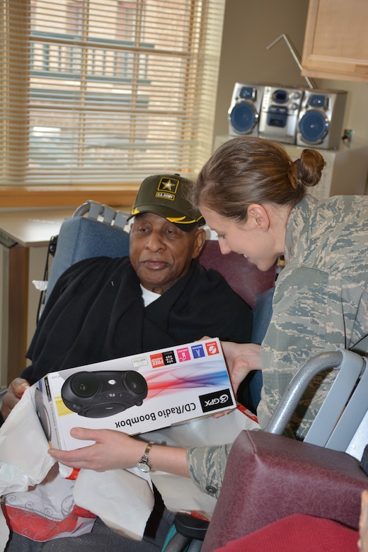 1st Lt Cristi Jordan, 507th Operations Group helps a resident of the Normans Veterans Center open a gift Dec. 22. (U.S. Air Force Photo/Maj. Jon Quinlan)