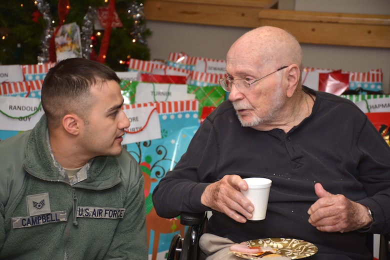 Staff Sgt. Anthony Campbell, 137th Air Refueling Wing, Oklahoma Air National Guard, listens to a veteran at the Norman Veterans Center Dec. 22.  (U.S. Air Force Photo/Maj. Jon Quinlan)