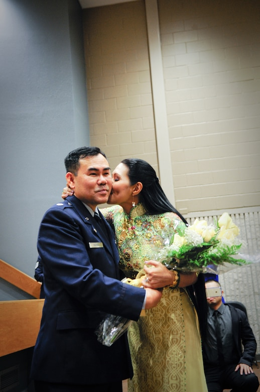Air Force Lt. Col. Don Nguyen, assistant director of operations for the 273rd Information Operations Squadron (IOS), Texas Air National Guard, is kissed by his wife, Huyen Vu, during his retirement ceremony in San Antonio, Nov. 23, 2014. Nguyen retired after 27 years of military service, including time with the Texas Army and Air National Guards. (U.S. Air National Guard photo by Tech. Sgt. Eric L. Wilson / Released) 141123-Z-IT549-004
