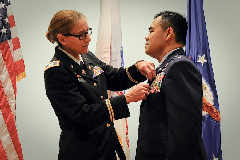 Army Col. Suzanne D. Adkinson, commander of the Texas Military Forces Joint Counterdrug Task Force, presents a medal to Air Force Lt. Col. Don Nguyen, assistant director of operations for the 273rd Information Operations Squadron (IOS), Texas Air National Guard, during his retirement ceremony in San Antonio, Nov. 23, 2014. Nguyen retired after 27 years of military service, including time with the Texas Army and Air National Guards. (U.S. Air National Guard photo by Tech. Sgt. Eric L. Wilson / Released) 141123-Z-IT549-001