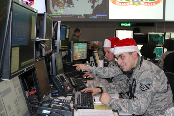 Staff Sgt. Nicholas Tharrett, pointing, and Staff Sgt. Andrew Washburn train for Christmas Eve Santa tracking operations at the Eastern Air Defense Sector.