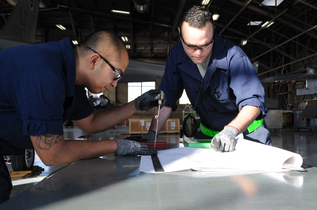 Staff Sgts. James Bacallo, left, and Joseph Gallegos analyze blueprints for an F-16D Fighting Falcon canopy seal longeron repair Dec. 11, 2014, at Luke Air Force Base, Ariz. The CSL strap is responsible for enhancing the structural integrity of the aircraft. Both Airmen are 309th Aircraft Maintenance Group depot structural maintenance specialists from Hill Air Force Base, Utah. (U.S. Air Force photo/Staff Sgt. Luther Mitchell Jr.)