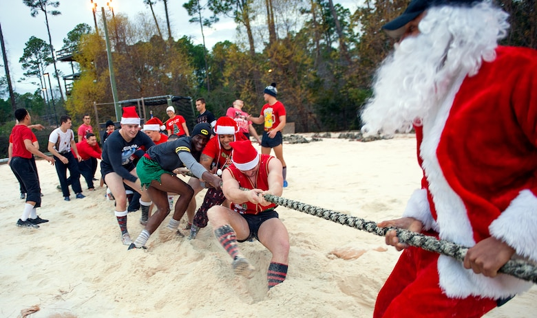 Tactical Air Control Party candidates face off against Santa and TACP instructors in a Tug-of-War competition during the annual TACP Christmas PT session on Hurlburt Field, Fla., Dec 19, 2014. More than 100 Tactical Air Control Party candidates and cadre, dressed as elves, Santa and one as a fairy during the PT session. (U.S. Air Force photo/ Staff Sgt. Kentavist P. Brackin)