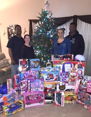 Master Sgt. Dontrel Daniels, 325th Aircraft Maintenance Squadron production superintendent, and wife Christina Daniels (left), and Staff Sgt. Gary Stewart, 95th Aircraft Maintenance Unit weapons load crew chief, and wife Michelle Stewart (right), stand by gifts donated to a family that needed some holiday cheer. The 325th AMXS holiday committee had funds left over and decided to donate what was left to a family. (U.S. Air Force courtesy photo)