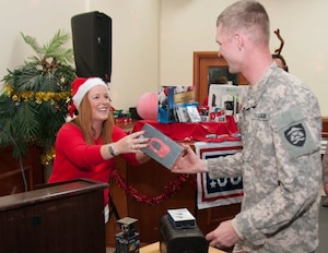 Priya Butler, director of operations, USO Southwest Asia, hands a set of Beats by Dre headphones to a soldier who won a raffle during a Christmas celebration in Baghdad, Iraq, Dec. 21, 2014. The 1st Infantry Division, the United States Department of State, the United Service Organizations, the New York Yankees and many other organizations, gathered more than 7,000 presents to show their support for Service members in Iraq.