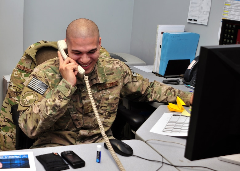U.S. Air Force Airman 1st Class Frank Perez-Castillo, 455th Expeditionary Security Forces Squadron Commander Support Staff, smiles during a surprise phone call from Chief Master Sgt. of the Air Force James A. Cody Dec. 24, 2014 at Bagram Airfield, Afghanistan. During the call, Cody expressed his well-wishes for the coming year and communicated his gratitude for Castillo-Perez's service. (U.S. Air Force photo by Staff Sgt. Whitney Amstutz/released)