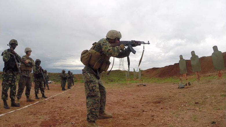 Burundi National Defense Force Soldiers observe as a Marine demonstrates firing from the standing position during a live fire range in Bujumbura, Burundi, Dec. 2, 2014. Marines and Sailors with Special Purpose Marine Air Ground Task Force Crisis Response-Africa trained alongside the Burundi National Defense Force where they advised the BNDF in the disciplines of logistics and engineering for approximately 3-months from October to December.