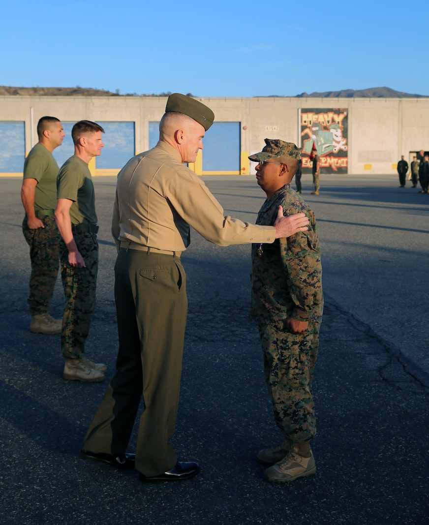 Major Gen. Vincent Coglianese, commanding general 1st Marine Logistics Group, congratulates Cpl. Ulises Zamoramartinez, an optics technician with 1st Maintenance Battalion, Combat Logistics Regiment 15, 1st MLG, during an award ceremony aboard Camp Pendleton, California, Dec. 19, 2014. Zamoramartinez, a 31-year-old native of Yakima, Washington, received the Purple Heart Medal for injuries received while deployed in Helmand province, Afghanistan, during a six-month tour with Georgian Liaison Team 10, Regional Command (Southwest). (Marine Corps photo by Cpl. Cody Haas/ Released)