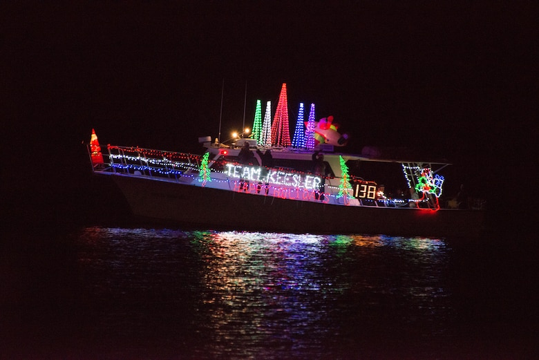 The Keesler Dolphin passes the judging boat during the 29th annual Christmas on the Water parade in Biloxi, Miss. Dec. 6, 2014. The boats, which parade along the gulf coast in full holiday décor, are judged by originality of theme, complexity of design, and overall appearance. Brig. Gen. Patrick Higby, 81st Training Wing commander, and his wife; Col. Dennis Scarborough, 81st TRW vice commander, and Maj. Carla Gleason, 81st TRW Public Affairs officer, were judges for the event. (U.S. Air Force photo by Marie Floyd)