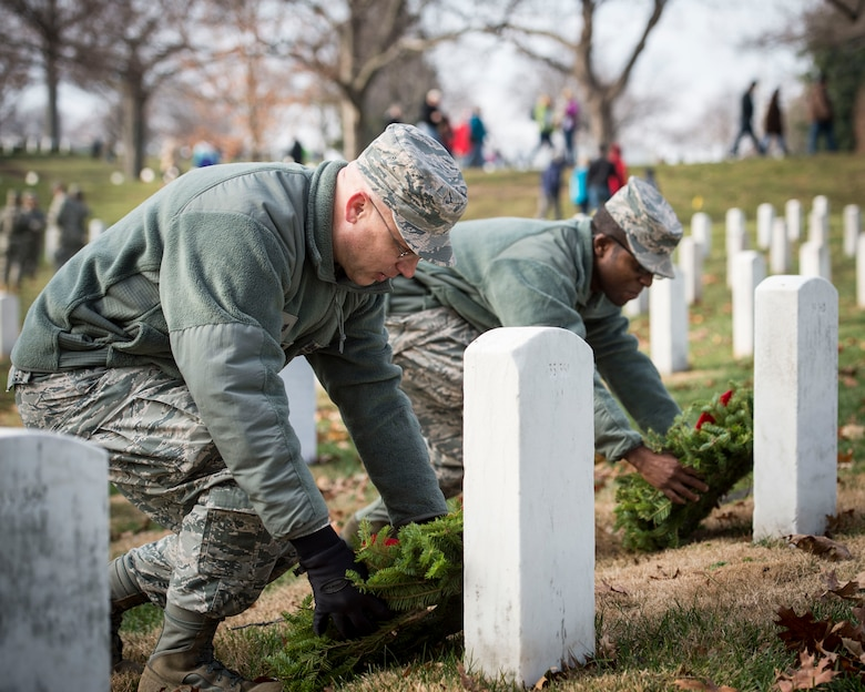 Tech. Sgt. Richy Kruger and Senior Airman James Arredon, Airmen assigned to Air Force Mortuary Affairs Operations at Dover Air Force Base, Delaware, place holiday wreaths on two graves at Arlington National Cemetery, Dec. 13, 2014. Both Kruger and Arredon said that volunteering to honor the fallen at Arlington was a natural extension of their duties at AFMAO. (U.S. Air Force photo by Captain Raymond Geoffroy/Released)