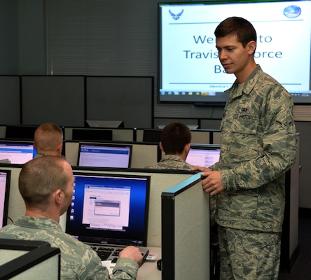 Air Force Airman Dimas Bernacchia assists an in-processing service member with a travel voucher at Travis Air Force Base, Calif., Dec. 10, 2014. Bernacchia holds dual citizenship in the United States and Italy. U.S. Air Force photo by Senior Airman Charles Rivezzo