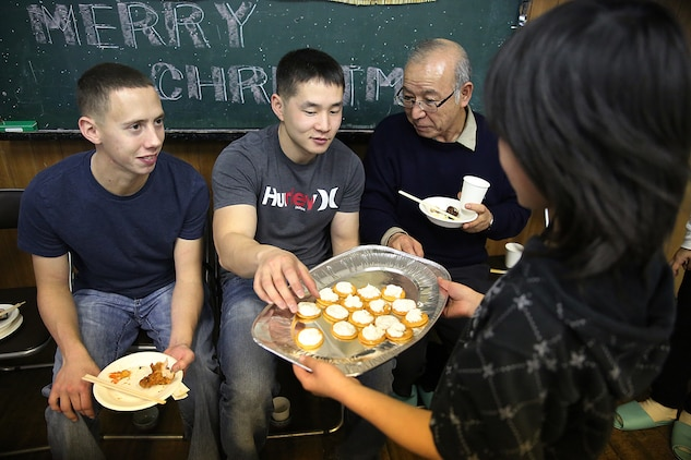 Cpl. Ruben Salinas, left, a resident Marine Air Ground Task Force planner for Marine Aircraft Group 12 aboard Marine Corps Air Station Iwakuni, Japan, and Cpl. Matthew Ahn, right, a chemical, biological, radiological and nuclear defense specialist with MAG-12, eat finger food made by the children from the Akebono children's home in Nasake Sima, Yamaguti, Dec. 23, 2014. As a part of giving back to the Japanese locals, MAG-12 Marines collected 777 cans of food from their unit holiday party to distribute to those in need. Four hundred of those cans went to the children's home that day.