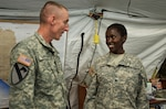 Army Maj. Gen. Gary Volesky recognizes Army Spc. Rysper Sirma for her exemplary performance while supporting Operation United Assistance at the Barclay Training Center, Monrovia, Liberia, Dec. 26, 2014. As a food inspection specialist, Sirma ensures the food and water her fellow service members consume are safe. U.S. Army photo by Staff Sgt. V. Michelle Woods