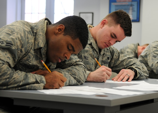 Airmen 1st Class Akeem Ferguson and Kevin Tufts fill out paperwork during their Unit Orientation Training Dec. 22, 2014, on F.E. Warren Air Force Base, Wyo. During the training, security forces members learn the basic skills they need to accomplish the mission.  Ferguson and Tufts are with the 90th Missile Security Forces Squadron. (U.S. Air Force photo/Airman 1st Class Malcolm Mayfield)