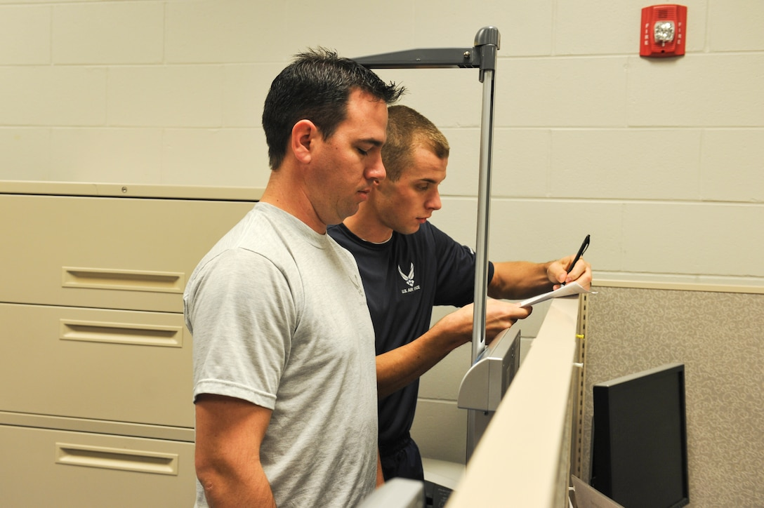 Senior Airman Andrew Muhlhahn, Fitness Assessment Cell augmentee, records the height and weight of SSgt Taylor Smith, 19th Special Operations Squadron special mission's aviator, at the Aderholt Fitness Center on Hurlburt Field, Fla., Dec. 31, 2014. The height and weight of Airmen are recorded in the event the body mass index is required. (U.S. Air Force photo/Airman 1st Class Jeff Parkinson)