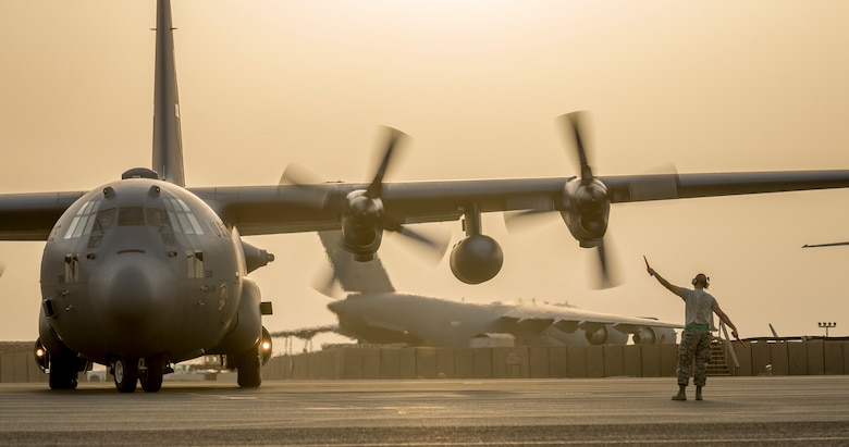 Senior Master Sgt. Kyle Klass marshals a C-130H Hercules from the 934th Air Wing after it landed at its new home Sept. 12, 2014, in Southwest Asia. The crew will be stationed with the 386th Air Expeditionary Wing for the next four months in support of Operation Enduring Freedom. Klass is the 386th Expeditionary Aircraft Maintenance Squadron dayshift production superintendent. (U.S. Air Force photo/Staff Sgt. Jeremy Bowcock)