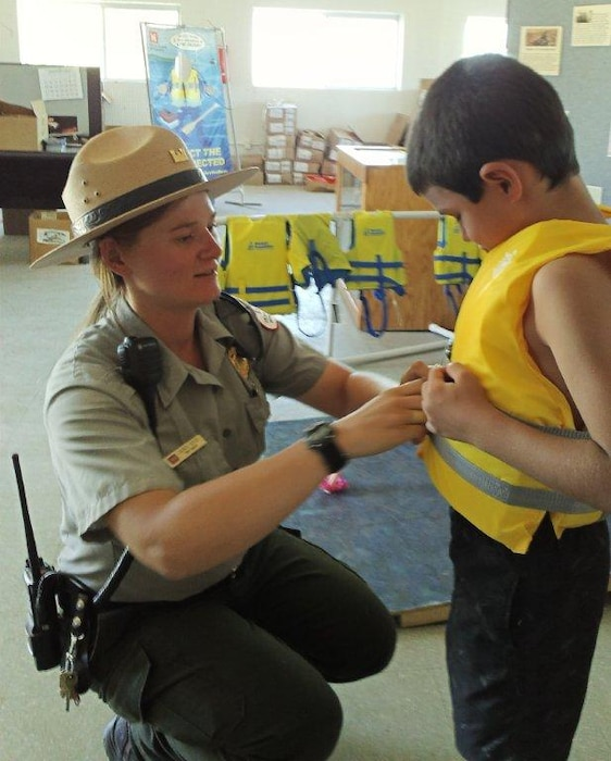 "2014 District Photo Drive entry. Photo by Valerie Mavis, Aug. 31, 2014.  ""Conchas Seasonal Park Ranger Lauren Boyer assists a young visitor with the proper fitting and wear of a U.S. Coast Guard-approved life jacket."""