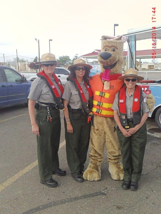 "Photo by Michael Vollmer, May 16, 2014.  ""Conchas Dam Lead Park Ranger Valerie Mavis (right) and Seasonal Rangers Ricky Haralson (far left) and Nadine Carter (2nd from left) assist volunteer Mathew Pacheco (Bobber) with a water safety event in Tucumcari, N.M."""