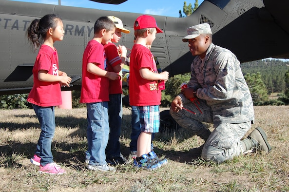Airman First Class William Booker, member of the Colorado Joint Counterdrug Task Force, passes out pencils to students at Ray Kilmer Elementary School, Colorado Springs, Colo. during their Red Ribbon Week October 21, 2014. Members of the CO-JCDTF and Drug Enforcement Agency flew into the schoolyard in a Colorado National Guard Blackhawk and talked to the children about making good choices to stay healthy and drug free. (U.S. Air National Guard photo by Capt. Kinder Blacke)