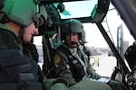 Air Force Maj. Mary Clark, right, instructs Air Force 1st Lt. David Shadoin during preflight procedures Dec. 16, 2014, at Kirtland Air Force Base, N.M. Clark is a UH-1N Huey instructor pilot and the 58th Operations Support Squadron's assistant director of operations, and Shadoin is a student pilot in the 512th Special Operations Squadron. Clark trained pilots for Afghanistan's air force during a yearlong deployment. U.S. Air Force photo by Jim Fisher