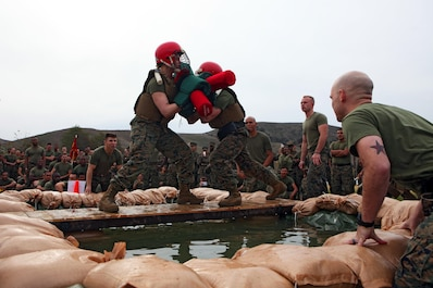 Marines with Combat Logistics Regiment 15, 1st Marine Logistics Group, face off in a pugil-stick match over three feet of water during the regiment's physical training competition aboard Camp Pendleton, Calif., Jan. 24, 2014. In addition to sparring with pugil sticks, the Marines participated in a boots and utilities formation run and competed in body jousting, an event in which Marines raced across a wet and soapy tarp with unit-decorated refrigerator boxes over their heads. The winner of the overall physical fitness competition was Maintenance Battalion.