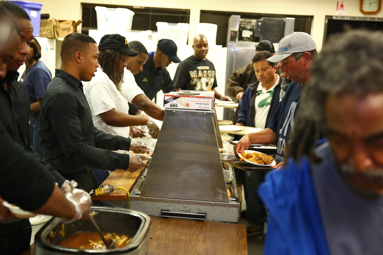 Servicemembers from Camp Pendleton and local volunteers serve food at the Bread of Life Rescue Mission in Oceanside, Calif., Jan. 28. Nine Marines and one sailor, with the help of several community volunteers, prepared and served a free dinner for local homeless and others in need at the Mission.